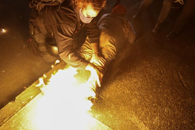A protester helps a man who caught fire from a Molotov cocktail thrown during a confrontation with Portland police in Portland, Oregon, U.S. September 5, 2020. (Photo by Caitlin Ochs/Reuters)