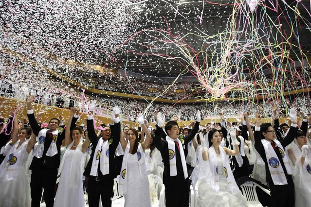 Newlyweds celebrate during a mass wedding ceremony of the Unification Church at Cheongshim Peace World Centre in Gapyeong, about 60 km (37 miles) northeast of Seoul February 17, 2013. The Unification Church founded by evangelist reverend Moon Sun-myung in Seoul in 1954, performed its first mass wedding in 1961 with 33 couples. Approximately 3,500 couples attended the mass wedding on Sunday. (Photo by Kim Hong-Ji/Reuters)