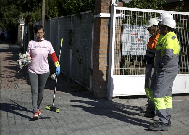 A s*x worker (L) cleaning the streets during a performance to denounce what they say is abuse and social stigma against them, walks past three workers in Madrid, Spain, October 14, 2015. (Photo by Andrea Comas/Reuters)