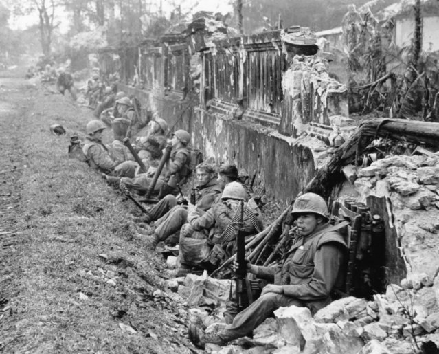 A unit of the 1st Battalion, 5th Regiment U.S. Marines, rests alongside a battered wall of Hue's imperial palace after a battle for the Citadel in February 1968, during the Tet Offensive. The Marines reported heavy casualties in street fighting in the ancient capital city of Vietnam. (Photo by AP Photo)