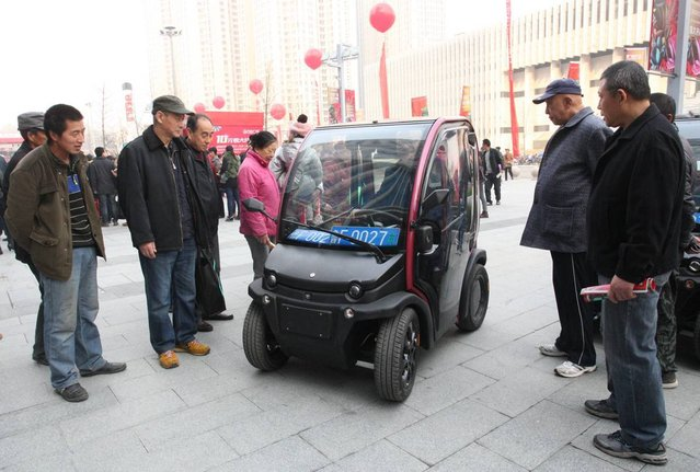 People look at a BIRO City Electric Vehicle designed by Shandong HTM new energy automobile manufacturing Co., Ltd. at Wanda Plaza on November 21, 2014 in Yantai, Shandong province of China. MIKI City Electric Vehicles are high power battery of environmental protection with travelling 150 kilometers in 5 degrees. (Photo by ChinaFotoPress via Getty Images)