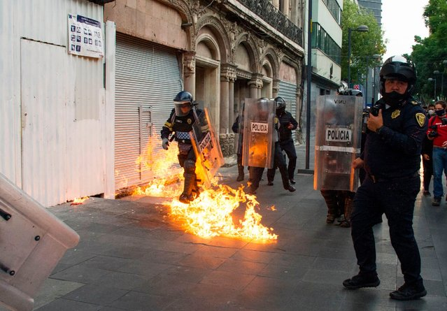 A policeman walks over a burning molotov cocktail thrown by demonstrators in Mexico City on September 26, 2020, during a march for the sixth anniversary of the disappearance of 43 students of the Ayotzinapa Teacher Training College. The students, who had commandeered five buses to travel to a protest, were stopped by municipal police in the city of Iguala, Guerrero. Prosecutors initially said the officers delivered the 43 teacher trainees to drug cartel hitmen, who killed them, incinerated their bodies and dumped the remains in a river. However, independent experts from the Inter-American Commission on Human Rights have rejected the government's conclusion. (Photo by Claudio Cruz/AFP Photo)
