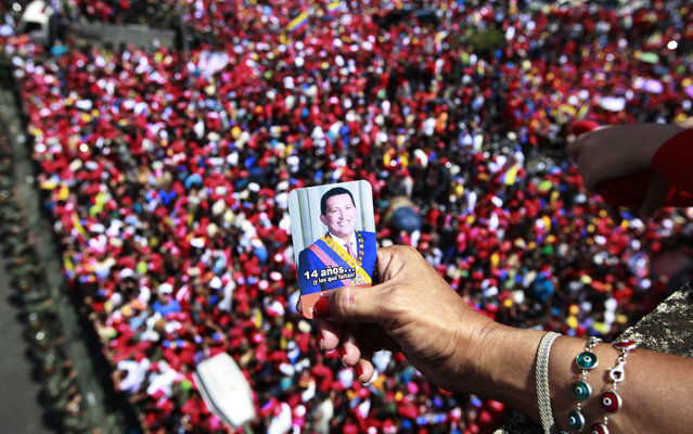 A supporter of Venezuela's late President Hugo Chavez holds a picture of him above a crowd waiting for Chavez's coffin to be taken from the hospital where he died on Tuesday, to a military academy where it will remain until his funeral in Caracas, Venezuela, Wednesday, March 6, 2013. Seven days of mourning were declared, all schools were suspended for the week and friendly heads of state were expected for an elaborate funeral Friday. (Photo by Ricardo Mazalan/AP Photo)