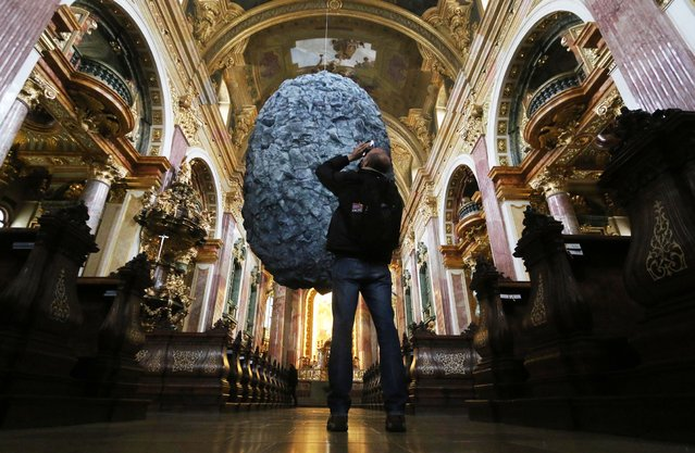 "A visitor takes a photo of a boulder plastic made of synthetic material called ""To be in Limbo"" hangs from the ceiling of the 20 meter high Jesuit Church in Vienna, Austria, Tuesday, November 25, 2014. (Photo by Ronald Zak/AP Photo)"