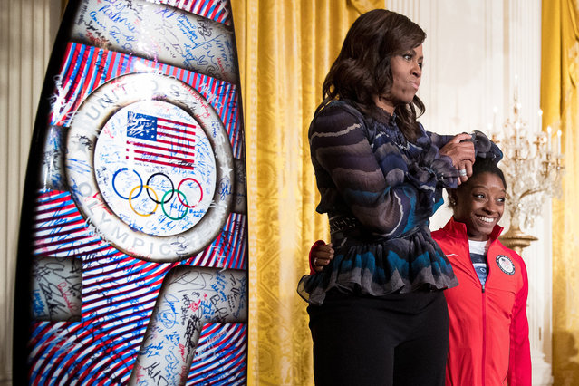 First lady Michelle Obama jokingly uses the head of US Olympics gymnast Simone Biles as an arm rest as they take the stage in the East Room of the White House in Washington, Thursday, Sept. 29, 2016, during a ceremony where President Barack Obama honored the 2016 United States Summer Olympic and Paralympic Teams. (AP Photo/Andrew Harnik)