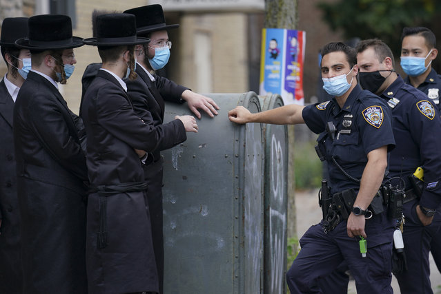 Members of the Orthodox Jewish community speak with NYPD officers, Wednesday, October 7, 2020, in the Borough Park neighborhood of the Brooklyn borough of New York. Gov. Andrew Cuomo moved to reinstate restrictions on businesses, houses of worship and schools in and near areas where coronavirus cases are spiking. Many neighborhoods that stand to be affected are home to large enclaves of Orthodox Jews. (Photo by John Minchillo/AP Photo)