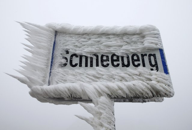 A sign for the village of Schneeberg, translated as Snow Mountain, is covered with ice, in northern Austria, December 3, 2014. (Photo by Heinz-Peter Bader/Reuters)