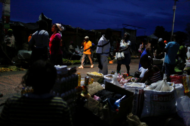 People buy goods at a street market while Hurricane Matthew approaches in Port-au-Prince, Haiti, October 2, 2016. (Photo by Carlos Garcia Rawlins/Reuters)