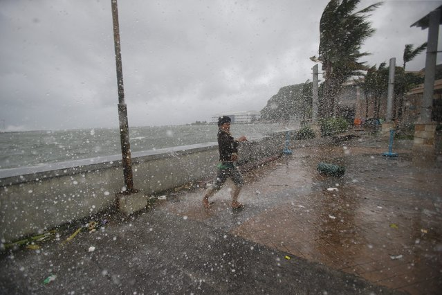 A man reacts as he strong winds and rain from Typhoon Hagupit hit shore in Legazpi, Albay province, eastern Philippines on Sunday, December 7, 2014. (Photo by Aaron Favila/AP Photo)