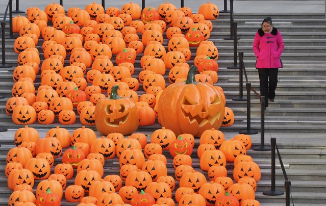 A woman walks down a stairway partially filled with decorations in the shape of carved pumpkins to celebrate Halloween in Shenyang, Liaoning province, China, October 30, 2015. (Photo by Reuters/Stringer)
