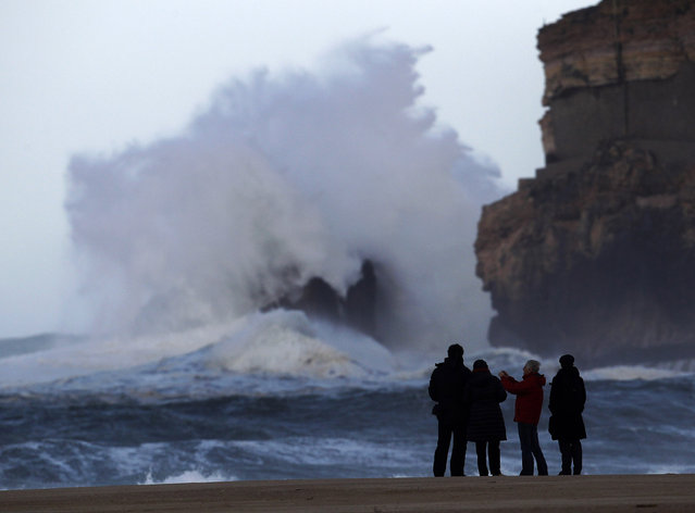 People take pictures of large waves at Nazare beach, December 25, 2013. (Photo by Rafael Marchante/Reuters)