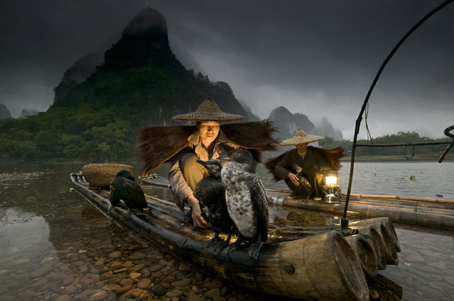 """Lit by lanterns, fishermen along the shores of the Li River prepare their cormorants for an evening of fishing. A tradition unique to Guangxi in south central China, fishermen have always trained the cormorants to dive after and catch fish attracted to the light of the lantern"". (Photo by Art Wolfe/Art Wolfe Stock)"