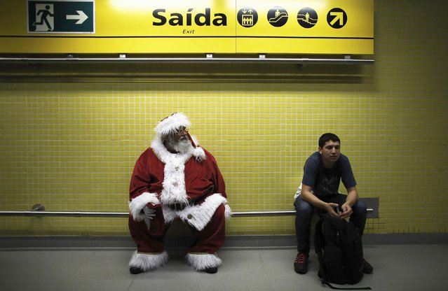 A man, dressed as Santa Claus, waits to board a train at a subway station as part of a promotional event by a bank in Sao Paulo December 12, 2014. (Photo by Nacho Doce/Reuters)