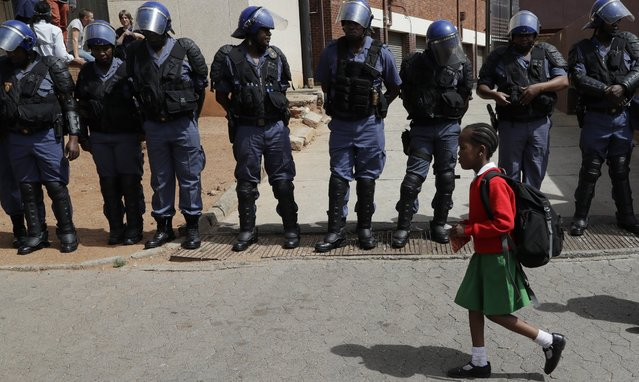A young girl wearing school uniform, walks past riot police officers as they guard students from the University of the Witswatersrand outside the Hillbrow Magistrat's Court in Johannesburg, South Africa, Wednesday, October 12, 2016, protesting in support of their peers who were arrested earlier this week. (Photo by Themba Hadebe/AP Photo)