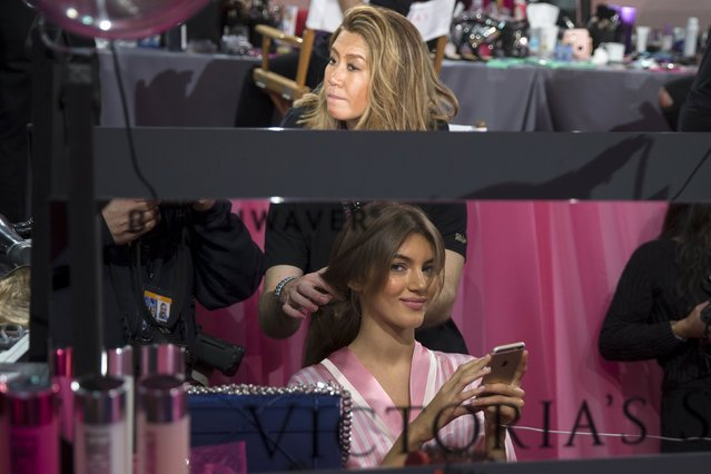 A model gets her hair done backstage before the Victoria's Secret Fashion Show in the Manhattan borough of New York November 10, 2015. (Photo by Carlo Allegri/Reuters)
