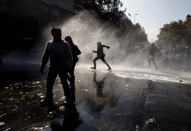People walk through the spray of a police water cannon after clashes broke out between protesters and security forces at the annual May Day march in Santiago, Chile. (Photo by Luis Hidalgo/Associated Press)