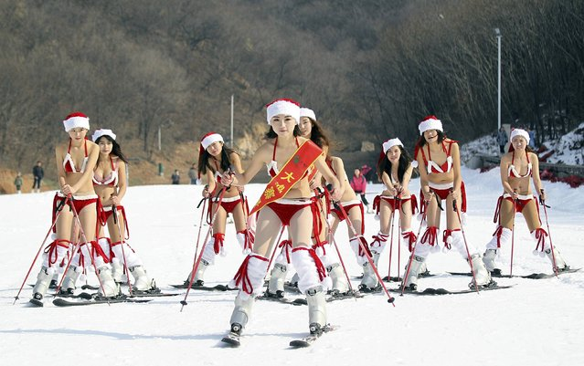 Women wearing bikinis and Santa Claus hats participate in a promotional event to celebrate the upcoming Christmas at a ski resort in Xuchang, Henan province, December 23, 2014. (Photo by Reuters/Stringer)