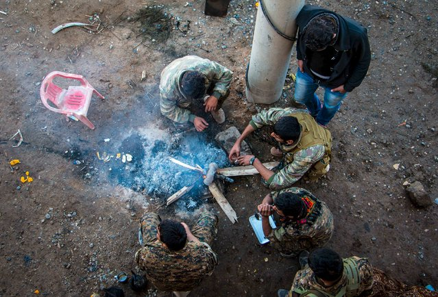 Rebel fighters from the Democratic Forces of Syria, gather around a fire near al-Hawl area where fighting between them and Islamic State fighters are taking place in south-eastern city of Hasaka, Syria November 10, 2015. Picture taken November 10, 2015. (Photo by Rodi Said/Reuters)