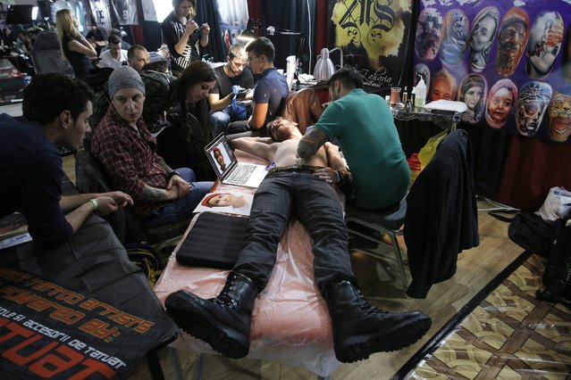 A customer gets a tattoo by Romanian tattoo artist Florin Zaharia (R) during a tattoo convention in Bucharest, Romania, 15 October 2016. (Photo by Robert Ghement/EPA)