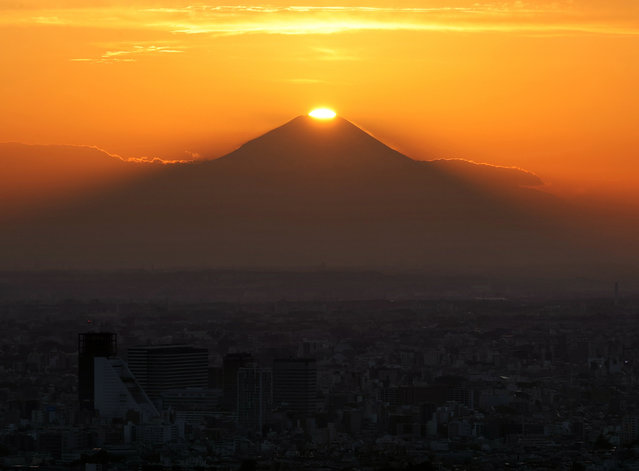 """The """"Diamond Fuji"""" is seen from a high rise building in the evening in Tokyo, Japan, 15 November 2020. The """"Diamond Fuji"""" phenomenon is when the sun is placed directly on the top of Mount Fuji. (Photo by JIJI Press/EPA/EFE)"""