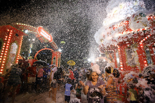 People enjoy the artificial snow made of foam at Tanglin Mall shopping centre on December 24, 2014 in Singapore. The mall has been holding the avalanche and snow show yearly as part of the Christmas festivities celebration in Singapore. (Photo by Suhaimi Abdullah/Getty Images)