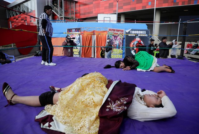 Cholitas wrestlers rest on the floor at the end of a fight during their return to the ring after the coronavirus disease (COVID-19) restrictions, in El Alto outskirts of La Paz, November 29, 2020. (Photo by David Mercado/Reuters)
