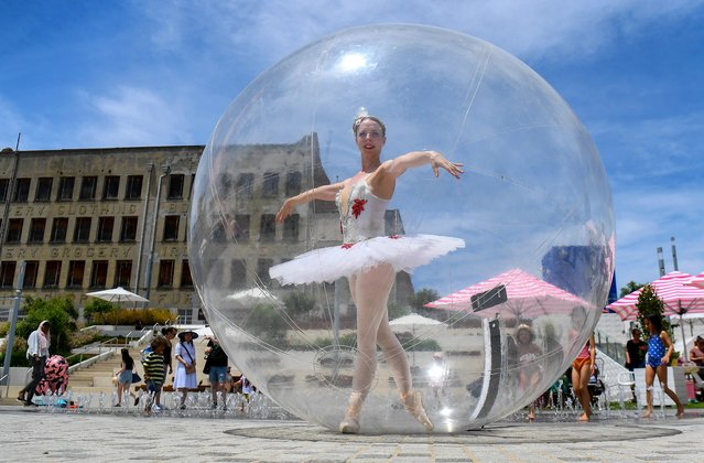 A ballet dancer poses in a giant plastic bubble as she entertains Christmas shoppers in Melbourne on December 13, 2020. (Photo by William West/AFP Photo)