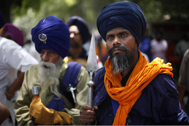 Indian Sikh Nihangs, part of an armed Sikh order, listen to a speaker, unseen, as they protest the acquittal of ruling Congress party leader Sajjan Kumar in New Delhi, India, Wednesday, May 8, 2013. An Indian court acquitted Kumar on April 30, of charges he incited mobs to kill Sikhs during the country's 1984 anti-Sikh riots. (Photo by Altaf Qadri/AP Photo)
