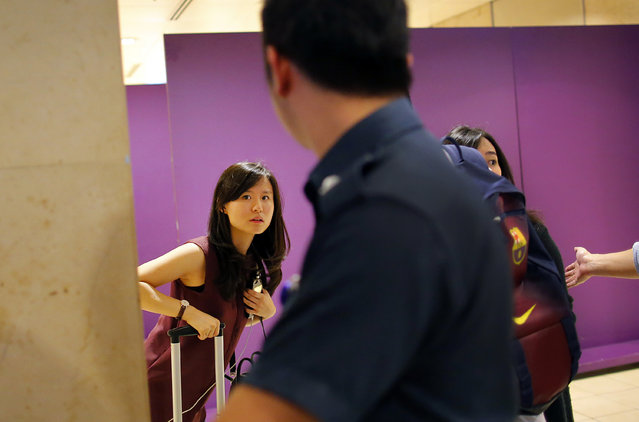 Louise Sidharta, left, from Indonesia, whose fiance was on board a missing AirAsia flight, arrives at a holding area for relatives and next-of-kin of passengers on that flight, at the Changi International Airport Sunday, December 28, 2014 in Singapore. An AirAsia plane disappeared on Sunday while flying over the Java Sea after taking off from Surabaya, Indonesia for Singapore. (Photo by Wong Maye-E/AP Photo)