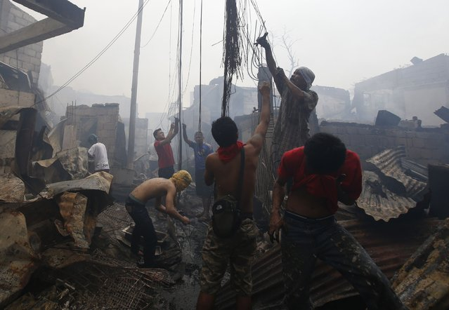 Residents recover copper from electric wires destroyed by a fire at a slum colony in Quezon city, Metro Manila January 1, 2015. (Photo by Erik De Castro/Reuters)