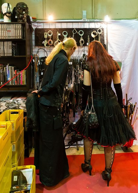 A couple looks at handcuffs and whips for sale at the Agra festival area on the first day of the annual Wave-Gotik Treffen, or Wave and Goth Festival, on May 17, 2013 in Leipzig, Germany. The four-day festival, in which elaborate fashion is a must, brings together over 20,000 Wave, Goth and steam punk enthusiasts from all over the world for concerts, readings, films, a Middle Ages market and workshops. (Photo by Marco Prosch)