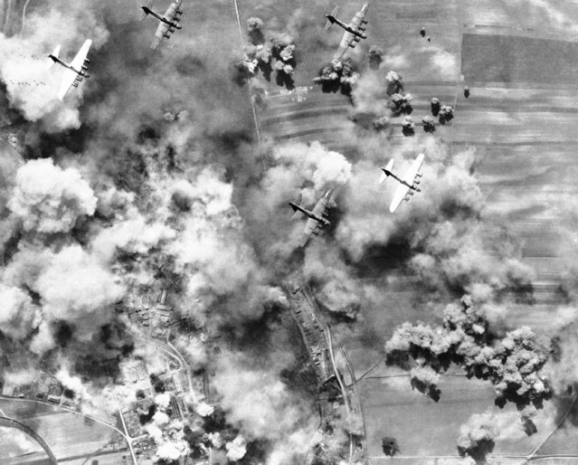 A formation of B-17 Flying Fortresses of the U.S. 15th Air Force flys on leaving a deadly hail of bombs of the important German Aircraft factory at Weiner Neustadt, south of Vienna Austria, May 3, 1944. Returning crews reported hits on the target, a large production center for Messerschmitt single-engined fighter planes. (Photo by AP Photo)