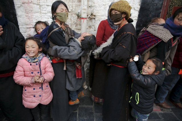 Tibetan pilgrims share a light moment as they wait to enter the Jokhang Temple in central Lhasa, Tibet Autonomous Region, China early November 20, 2015. (Photo by Damir Sagolj/Reuters)