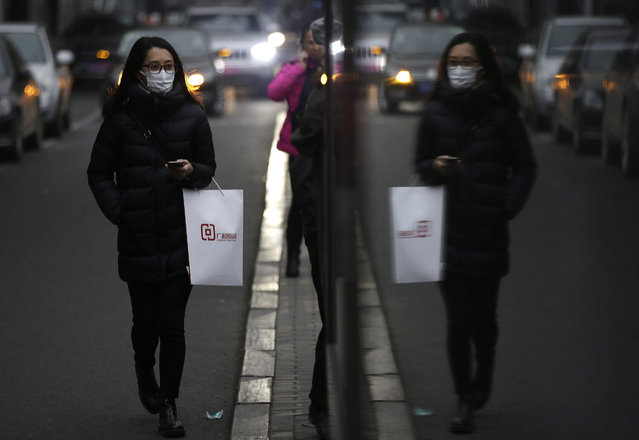 A Chinese woman wearing a mask is reflected in a glass panel on a smoggy day in Beijing, China, 11 November 2015. Beijing's Environmental Protection Bureau warned of poor air quality that could continue in the coming days. Heavy smog of hazardous levels had affected China's north and northeast regions beginning 08 November. (Photo by How Hwee Young/EPA)