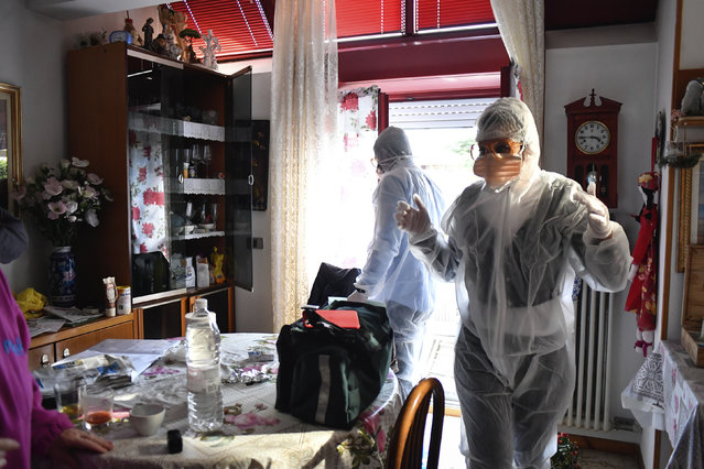 Medical staffers wearing protective gear, part of a special unit performing house calls, work in Bergamo, northern Italy, one of the areas worse-affected by coronavirus, Wednesday, March 25, 2020. (Photo by Claudio Furlan/LaPresse via AP Photo)