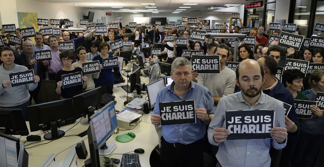 "Journalists hold placard reading ""I am Charlie"" as they hold a minute of silence, on January 7, 2015 at the redaction of French news agency Agence France Presse, following the attack by gunmen in the offices of the French satirical weekly Charlie Hebdo. (Photo by Bertrand Guay/AFP Photo)"