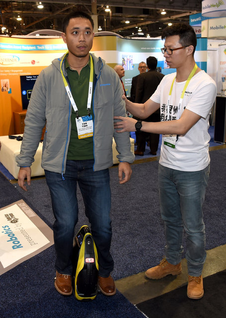Yan Ting (L) gets help riding an InMotion SCV R3 self-balancing cycle from InMotion's Guo Yu at the 2015 International CES at the Sands Expo and Convention Center on January 6, 2015 in Las Vegas, Nevada. The personal transport device can be controlled with an App by with a smartphone or tablet. (Photo by Ethan Miller/Getty Images)