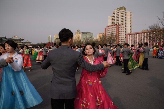 "Students participate in a ""mass dance"" event outside the Pyongyang Indoor Stadium in Pyongyang on April 9, 2018. Thousands of North Koreans gathered in locations across Pyongyang to dance celebration of late leader Kim Jong Il. (Photo by Ed Jones/AFP Photo)"