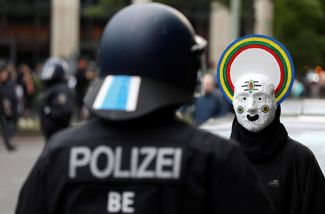 A protestor wearing a mask and a police officer face off during a demonstration on May Day, amid the spread of the coronavirus disease (COVID-19), in Berlin, Germany on May 1, 2020. (Photo by Christian Mang/Reuters)