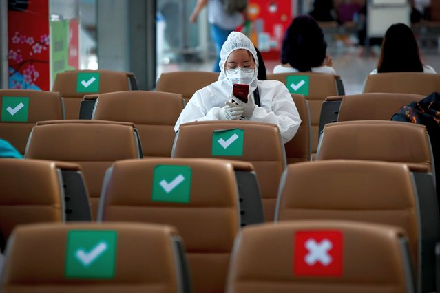 A woman in a hazmat suit sits in chairs marked with social distancing stickers at the Suvarnabhumi International Airport amid a new wave of the coronavirus disease (COVID-19) pandemic in Bangkok, Thailand, 05 January 2021. The Thai government ordered a nationwide partial business shutdowns for 28 'red zones' provinces including Bangkok as part of stricter measures to curb the new wave of the infectious disease. Travelers flying between Thai provinces could face additional health screening, and international flights from the UK have been put on hold. Thai authorities recorded 745 new cases with 709 being local infections, making it the highest number of daily infections since the start of the pandemic. (Photo by Diego Azubel/EPA/EFE)