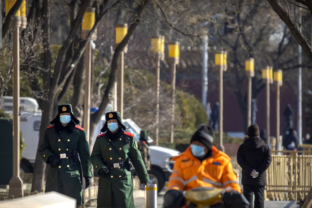 Chinese paramilitary police wearing face masks to protect against the spread of the coronavirus patrol along a street in Beijing, Saturday, January 9, 2021. COVID vaccine shots will be free in China, where more than 9 million doses have been give to date, health officials in Beijing said Saturday. (Photo by Mark Schiefelbein/AP Photo)