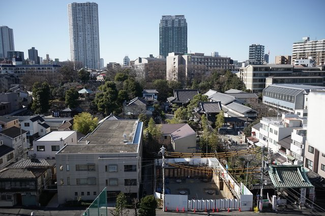 In this January 8, 2015 photo, Sengakuji temple and the condominium construction site are seen in Tokyo. (Photo by Eugene Hoshiko/AP Photo)