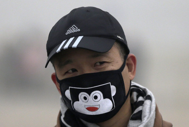 In this December 1, 2015 photo, a man wears a mask to protect himself from pollutants near Tiananmen Gate on a heavily polluted day in Beijing. (Photo by Andy Wong/AP Photo)