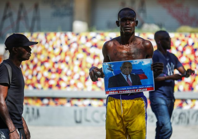 A man holds a photograph of Supreme Court Judge Joseph Mecene Jean-Louis during protests against Haiti's President Jovenel Moise in Port-au-Prince, Haiti on February 8, 2021. (Photo by Jeanty Junior Augustin/Reuters)