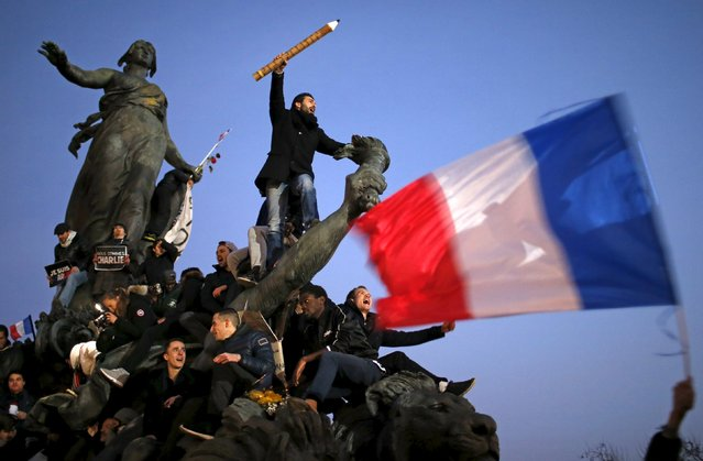 """A man holds a giant pencil as he takes part in a solidarity march in the streets of Paris after theCharlie Hebdo shootings, France January 11, 2015. Stephane Mahe: I covered the arrival of the heads of state at the start of the solidarity march. I then made my way through the streets, which were packed with people holding """"Je suis Charlie"""" banners, to the Place de la Nation. (Photo by Stephane Mahe/Reuters)"""