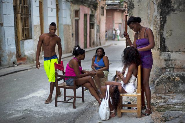Hairdresser Lisandra works on a woman's extensions as others wait their turn in Old Havana, Cuba, Tuesday, January 13, 2015. Lisandra attends her clients on the sidewalk outside her home. (Photo by Ramon Espinosa/AP Photo)