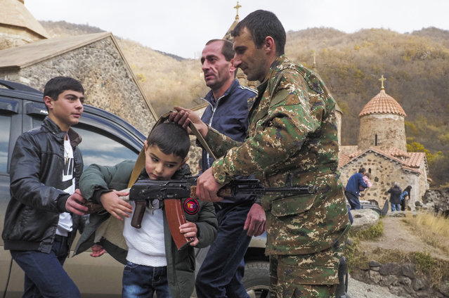 People shows a Kalashnikov gun to a boy at the Dadivank, an Armenian Apostolic Church monastery dating to the 9th century, as ethnic Armenians leave the separatist region of Nagorno-Karabakh to Armenia, Saturday, November 14, 2020. The territory is to be turned over to Azerbaijan on Sunday as part of territorial concessions in an agreement to end six weeks of intense fighting with Armenian forces. Hundreds of thousands of Azeris were displaced by the war that ended in 1994. It is unclear when any civilians might try to settle in Karvachar — which will now be known by its Azeri name Kalbajar — or elsewhere. (Photo by Dmitry Lovetsky/AP Photo)