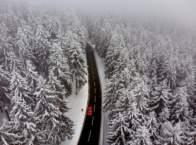 A car drives between snow covered trees in the Taunus region near Frankfurt, Germany, Tuesday, December 8, 2020. (Photo by Michael Probst/AP Photo)