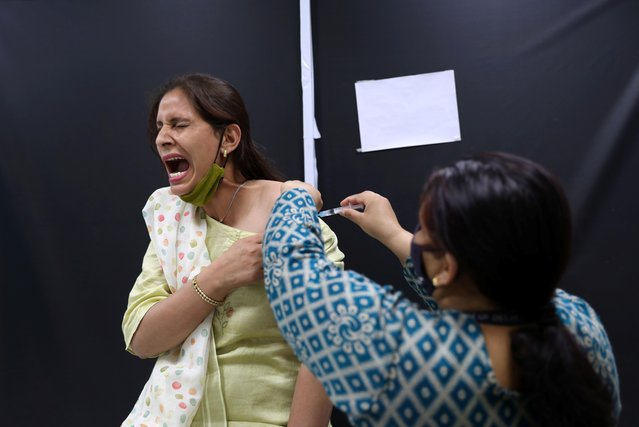 A frontline worker reacts as she receives a dose of AstraZeneca's COVISHIELD vaccine, produced by the Serum Institute of India, during the coronavirus disease (COVID-19) vaccination campaign at a medical centre in New Delhi, India, February 24, 2021. (Photo by Anushree Fadnavis/Reuters)