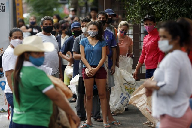People wearing masks amid the COVID-19 pandemic line up for bags of food, like peanuts, cassava and corn, from farming women representing the For a New Paraguay Party political party in Asuncion, Paraguay, Wednesday, February 24, 2021. The food giveaway marks National Women's Day and commemorate the first American Women's Assembly, held in the capital in 1867. (Photo by Jorge Saenz/AP Photo)